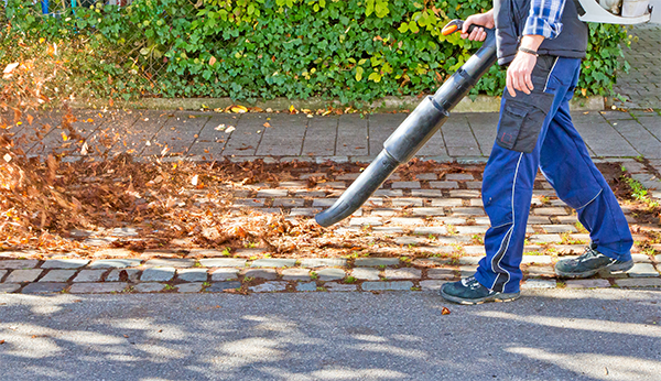Image of a man's legs walking with leaf blower